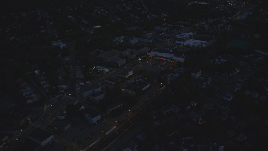 6k stock footage aerial video flying by a strip mall, Hyde Park, Massachusetts, night Aerial Stock Footage | AX146_159