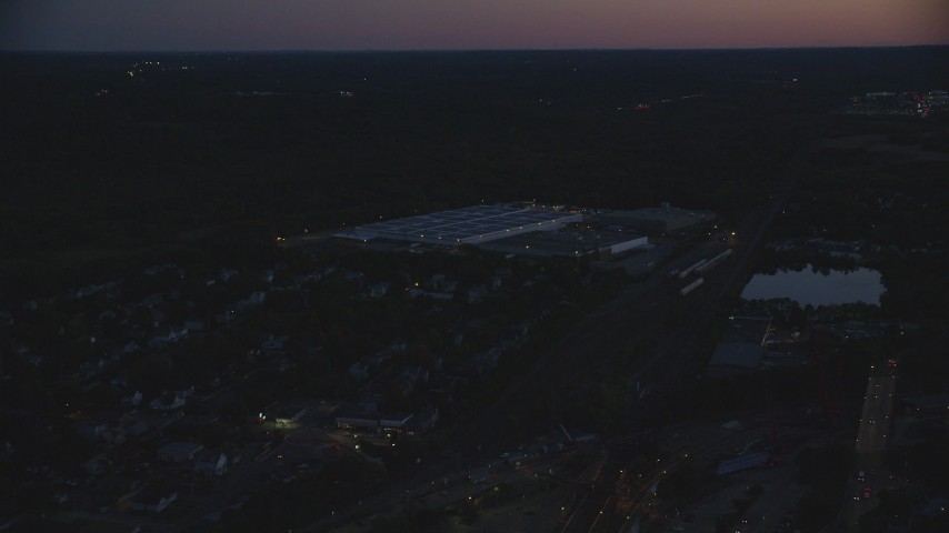6k stock footage aerial video flying by a large warehouse, Hyde Park, Massachusetts, night Aerial Stock Footage | AX146_160
