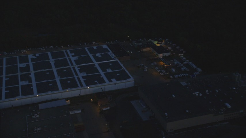 6k stock footage aerial video flying by a large warehouse, Hyde Park, Massachusetts, night Aerial Stock Footage | AX146_161