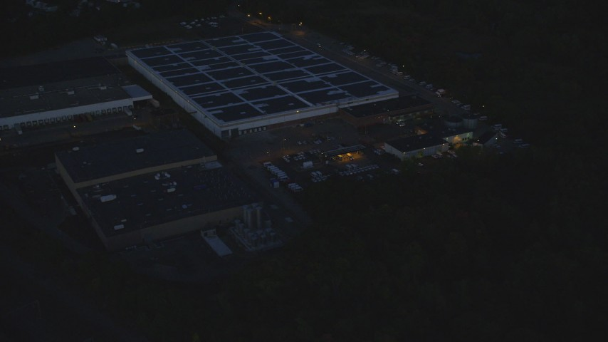 6k stock footage aerial video flying away from a large warehouse, Hyde Park, Massachusetts, night Aerial Stock Footage | AX146_162
