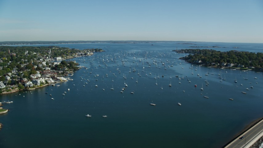 6k stock footage aerial video flying along a coastal community and boats in the harbor, Marblehead Harbor, Marblehead, Massachusetts Aerial Stock Footage | AX147_024