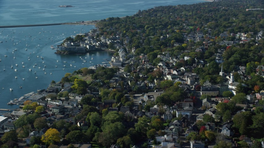 6k stock footage aerial video flying over a coastal community with trees along the harbor, Marblehead, Massachusetts Aerial Stock Footage | AX147_027