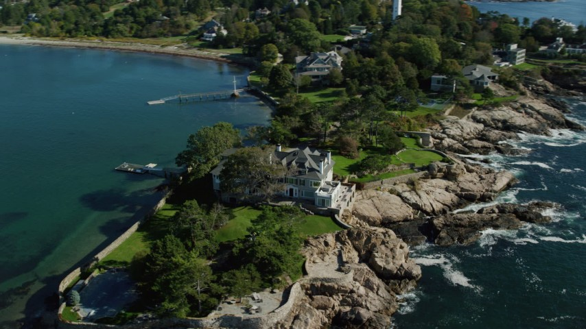6k stock footage aerial video orbiting an oceanfront mansion along Lobster Cove, Manchester-by-the-Sea, Massachusetts Aerial Stock Footage | AX147_062