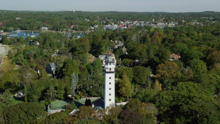6k stock footage aerial video flying over a light house and coastal community among trees, Manchester-by-the-Sea, Massachusetts Aerial Stock Footage | AX147_065