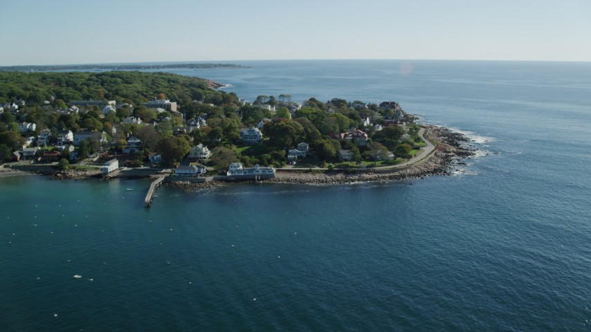 Flying by oceanfront hoes, rocky coast, Gloucester, Massachusetts Aerial Stock Footage | AX147_079