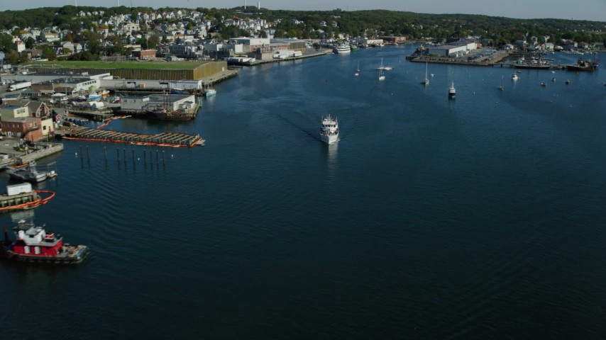 Tracking a ferry by a small coastal town, Gloucester, Massachusetts Aerial Stock Footage | AX147_088
