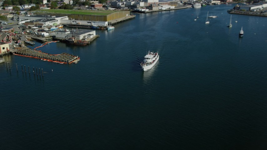 6k stock footage aerial video tracking a ferry by a small coastal town, Gloucester, Massachusetts Aerial Stock Footage | AX147_088