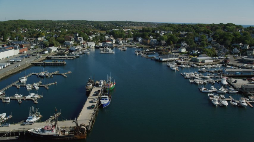 Flying over a small harbor, approach coastal town, Gloucester, Massachusetts Aerial Stock Footage | AX147_089
