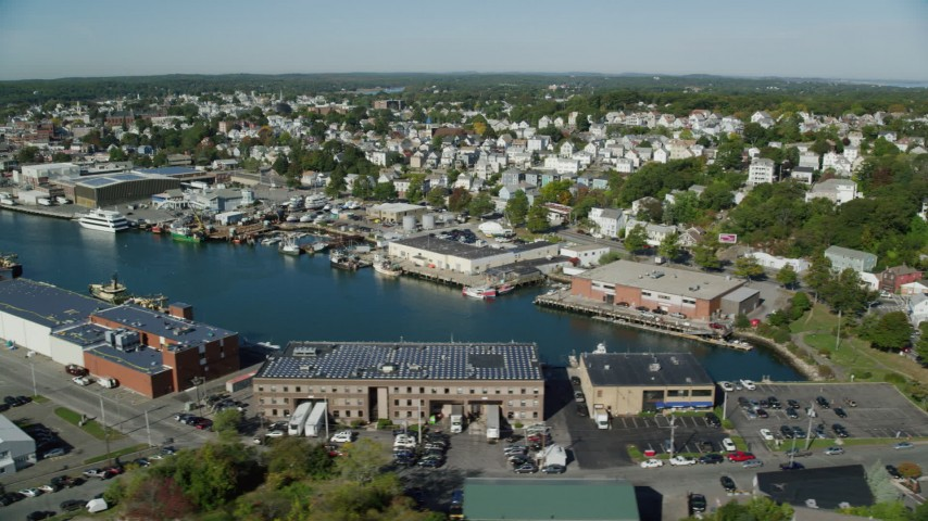 Flying by coastal town, warehouses, Gloucester, Massachusetts Aerial Stock Footage | AX147_090