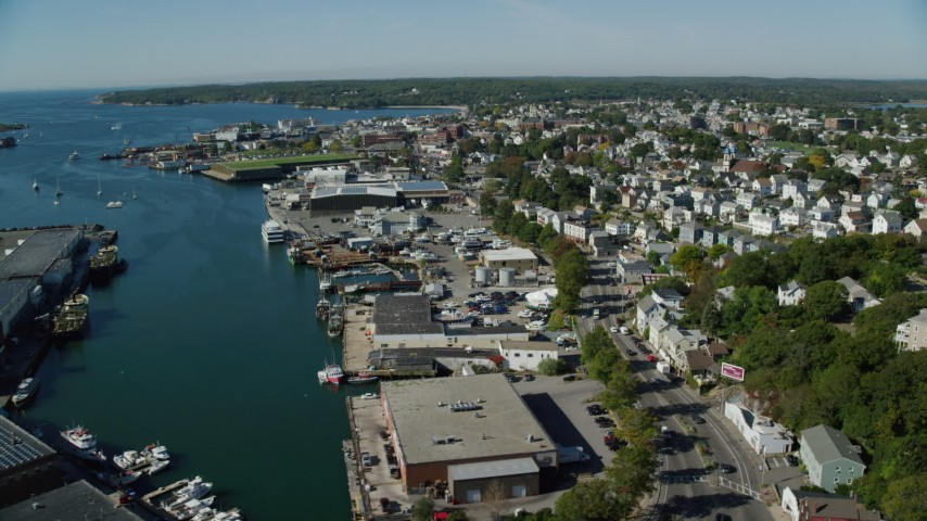 Flying by a coastal town, small harbor, Gloucester, Massachusetts Aerial Stock Footage | AX147_091