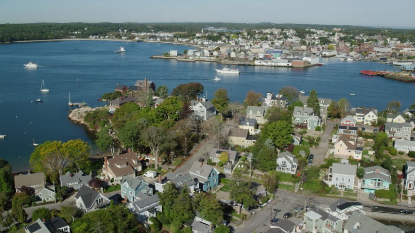 Flying by coastal town, revealing a small factory, boats, Gloucester, Massachusetts Aerial Stock Footage   AX147_097