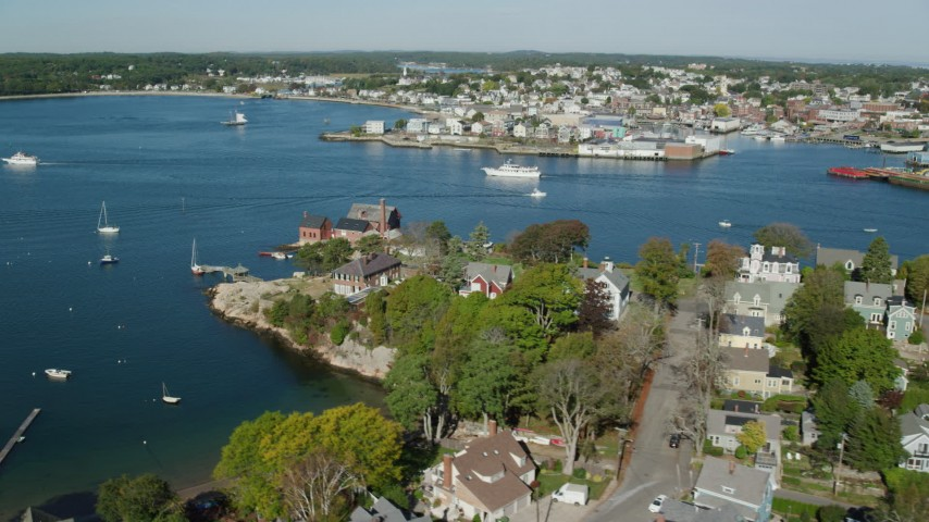 6k stock footage aerial video flying by coastal town, revealing a small factory, boats, Gloucester, Massachusetts Aerial Stock Footage | AX147_097