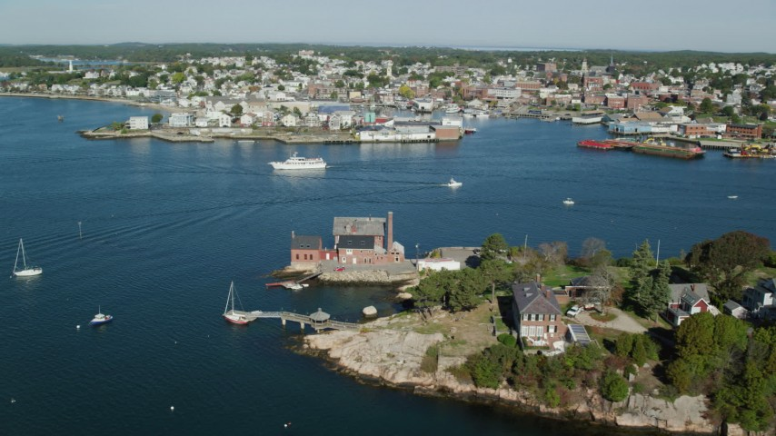 Flying by coastal town, small factory, boats in the harbor, Gloucester, Massachusetts Aerial Stock Footage | AX147_098