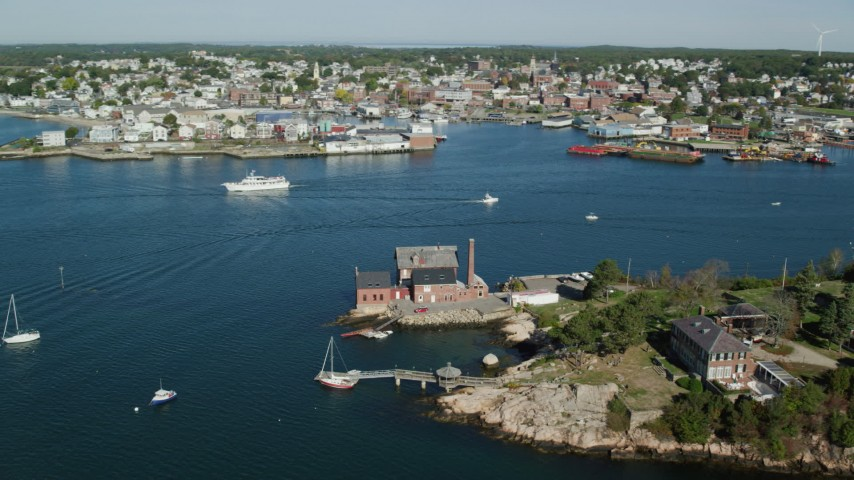 6k stock footage aerial video flying by coastal town, small factory, boats in the harbor, Gloucester, Massachusetts Aerial Stock Footage | AX147_098