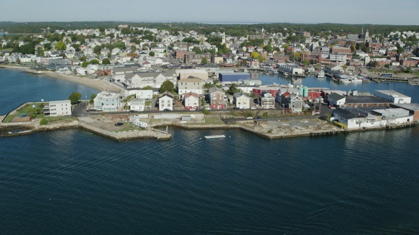 Approaching and flying over coastal town, warehouses, Gloucester, Massachusetts Aerial Stock Footage   AX147_099