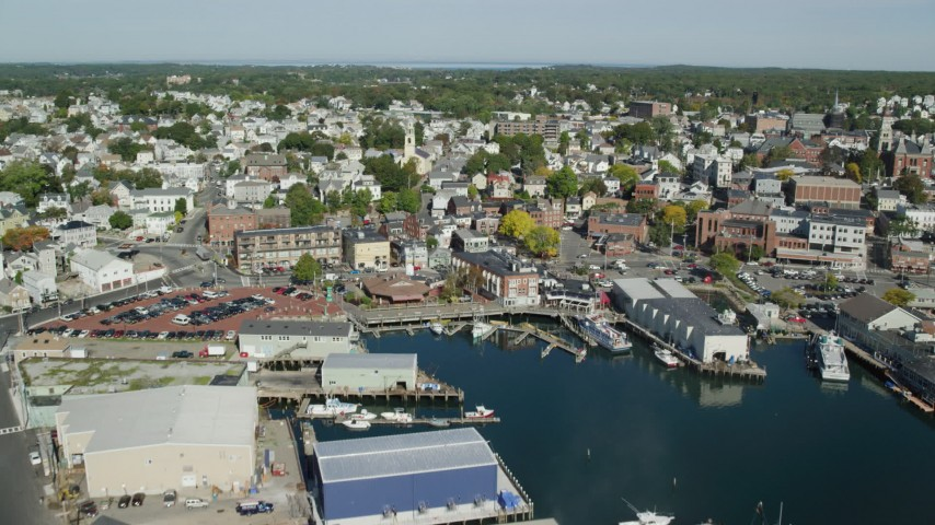 6k stock footage aerial video approaching and flying over coastal town, warehouses, Gloucester, Massachusetts Aerial Stock Footage | AX147_099