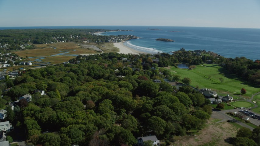 Fly over trees and coastal community toward beaches, Gloucester, Massachusetts Aerial Stock Footage AX147_106