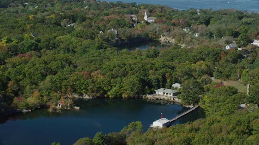 Fly over trees, pond and church in small coastal town, autumn, Gloucester, Massachusetts Aerial Stock Footage | AX147_131