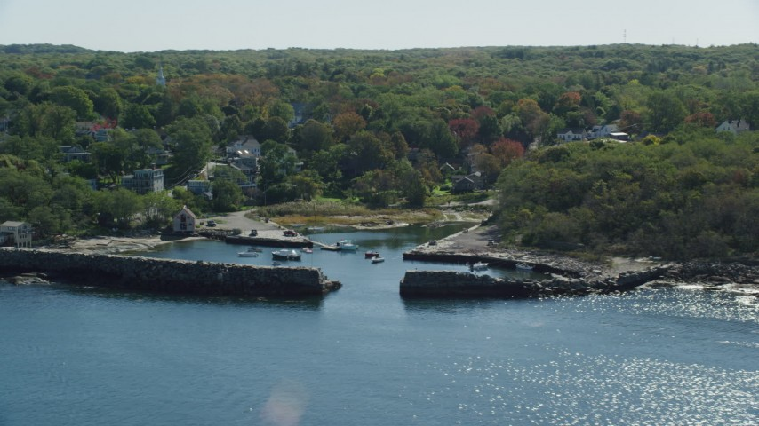 Fly away from small coastal town among autumn trees, Gloucester, Massachusetts Aerial Stock Footage | AX147_134