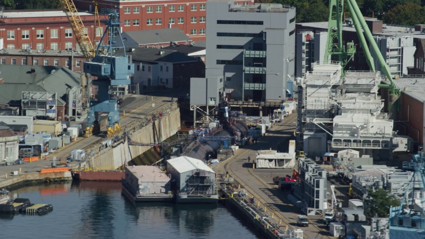 6k aerial video flying by a submarine in a naval shipyard, Kittery, Maine Aerial Stock Footage | AX147_188