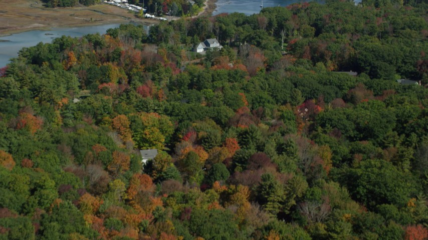6k aerial video flying over colorful forest, rural homes, reveal York Harbor, Kittery and York, Maine Aerial Stock Footage | AX147_230