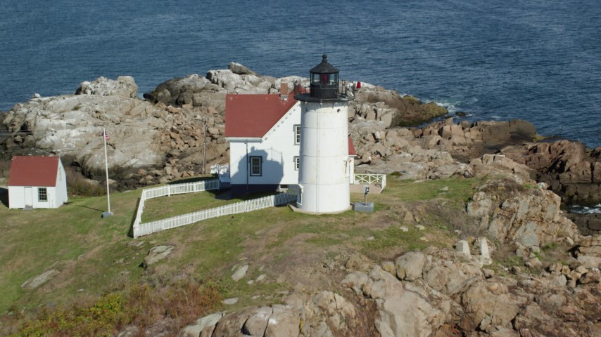 6k stock footage aerial video approaching Cape Neddick Light, tilt down, fly over, York, Maine Aerial Stock Footage | AX147_237