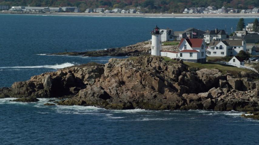 6k stock footage aerial video orbiting Cape Neddick Light, coastal town, autumn, York, Maine Aerial Stock Footage | AX147_239