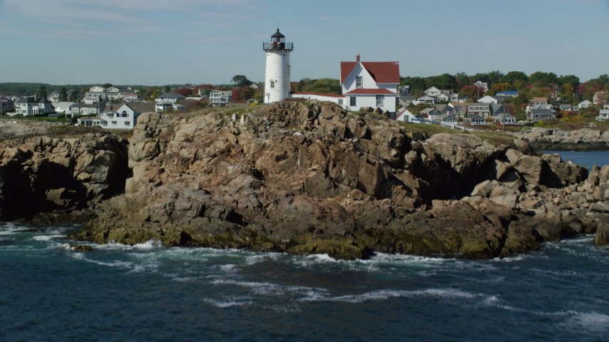 6k stock footage aerial video flying low over water, tilt up to reveal Cape Neddick Light, York, Maine Aerial Stock Footage AX147_241 | Axiom Images