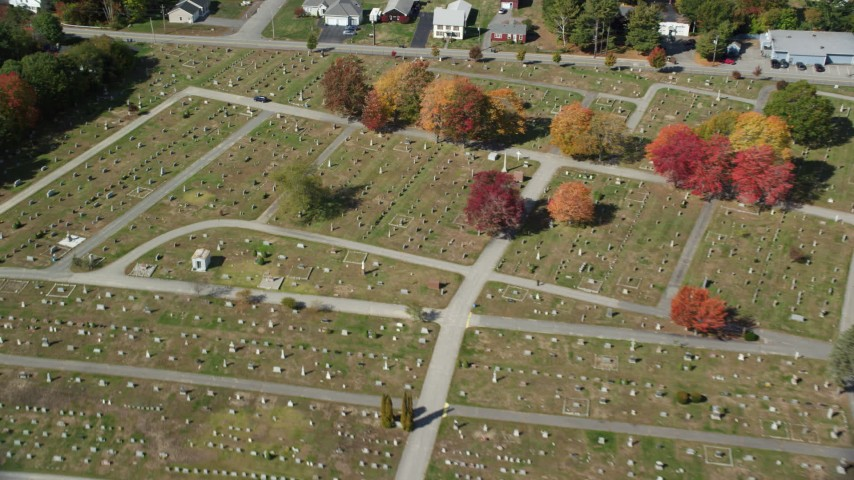 6k stock footage aerial video flying over dense, colorful forest, rural homes, approach cemetery, Biddeford, Maine Aerial Stock Footage | AX147_279
