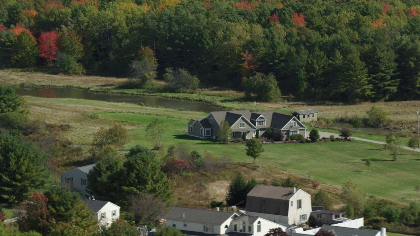 6k aerial video flying by riverfront rural homes, colorful forest, Biddeford, Maine Aerial Stock Footage | AX147_290