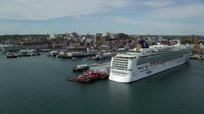 6k aerial video flying by docked cruise ship, piers and downtown, autumn, Portland, Maine Aerial Stock Footage | AX147_322