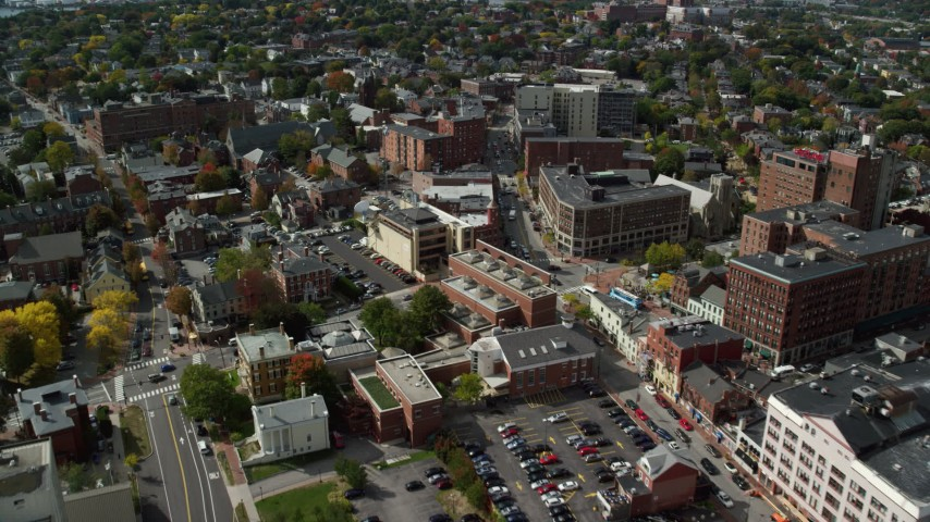 6k aerial video flying over office buildings, approach tv station, apartments, autumn, Portland, Maine Aerial Stock Footage | AX147_335