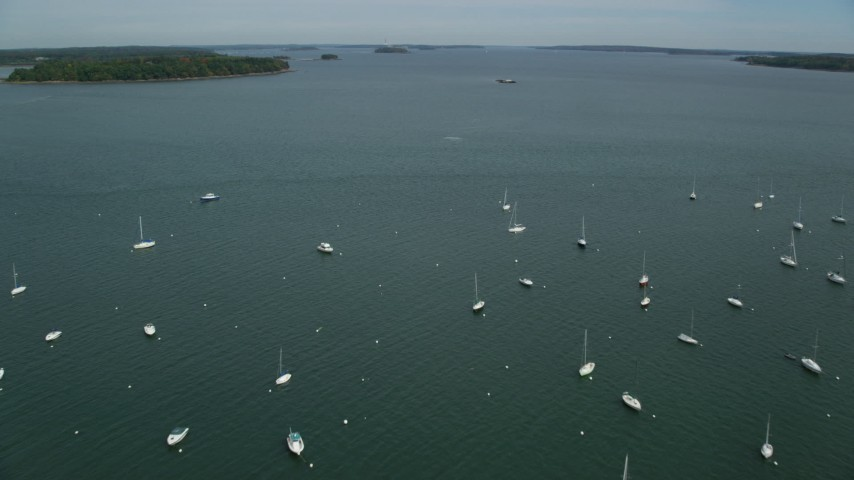 6k stock footage aerial video approaching and fly over boats moored in the bay, Portland, Maine Aerial Stock Footage | AX147_343