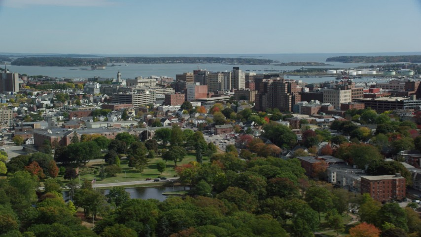6k aerial video flying by downtown office buildings, colorful autumn trees, Portland, Maine Aerial Stock Footage | AX147_357