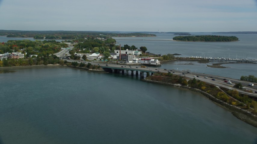 6k aerial video approaching Tukey's Bridge, Interstate 295, small factory, Portland, Maine Aerial Stock Footage | AX147_359