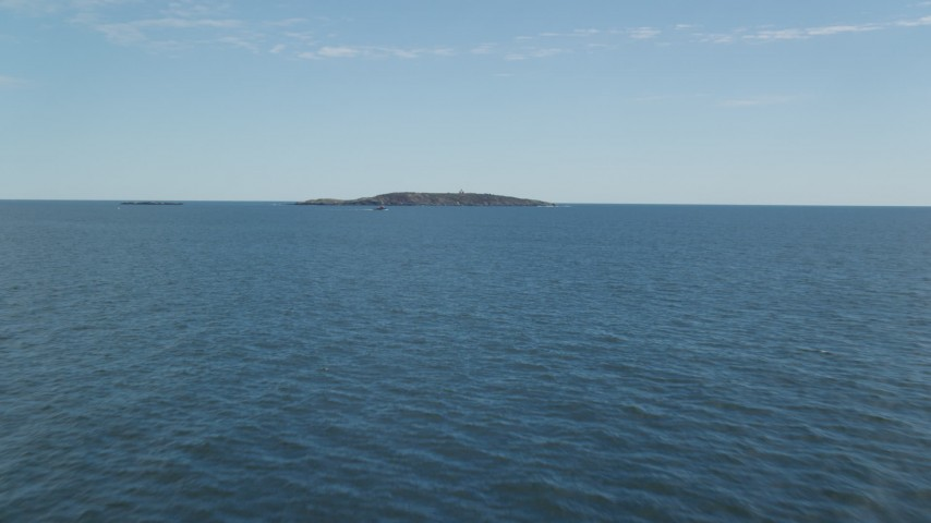 6k stock footage aerial video flying low over the ocean approaching boat and Seguin Island, Phippsburg, Maine Aerial Stock Footage | AX147_386