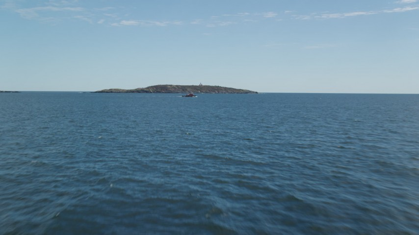 6k stock footage aerial video flying low over ocean, approaching a boat and Seguin Island, Phippsburg, Maine Aerial Stock Footage | AX147_387