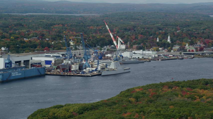 6k aerial video flying by waterfront General Dynamics Bath Iron Works, autumn, Bath, Maine Aerial Stock Footage | AX147_410