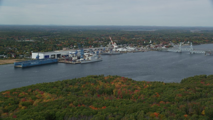6k aerial video flying by waterfront General Dynamics Bath Iron Works, autumn, Bath, Maine Aerial Stock Footage | AX147_411