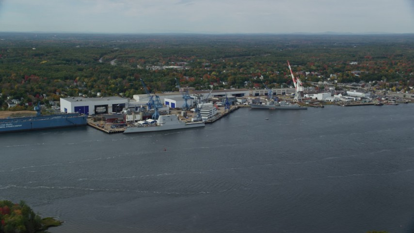 6k aerial video flying by waterfront General Dynamics Bath Iron Works, autumn, Bath, Maine Aerial Stock Footage AX147_412