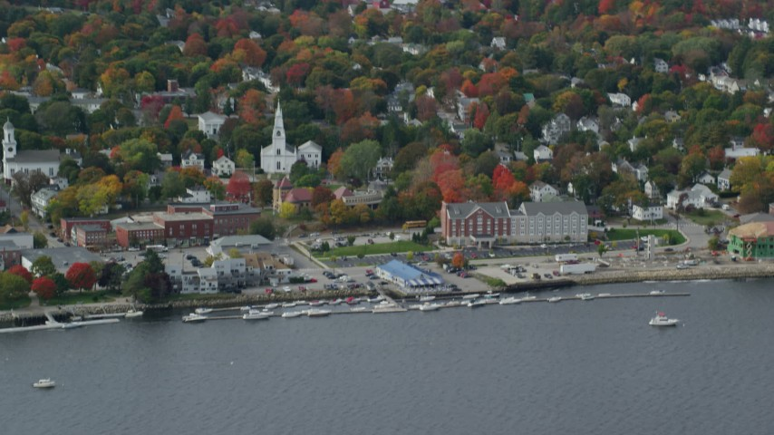 6k aerial video flying by small waterfront town, church, autumn, Bath, Maine Aerial Stock Footage | AX147_414