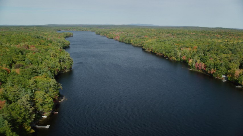 6k aerial video flying by a colorful forest, over Biscay Pond, autumn, Damariscotta, Maine Aerial Stock Footage | AX148_022