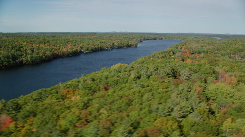 6k aerial video flying by a colorful forest, Biscay Pond, autumn, Damariscotta, Maine Aerial Stock Footage | AX148_023