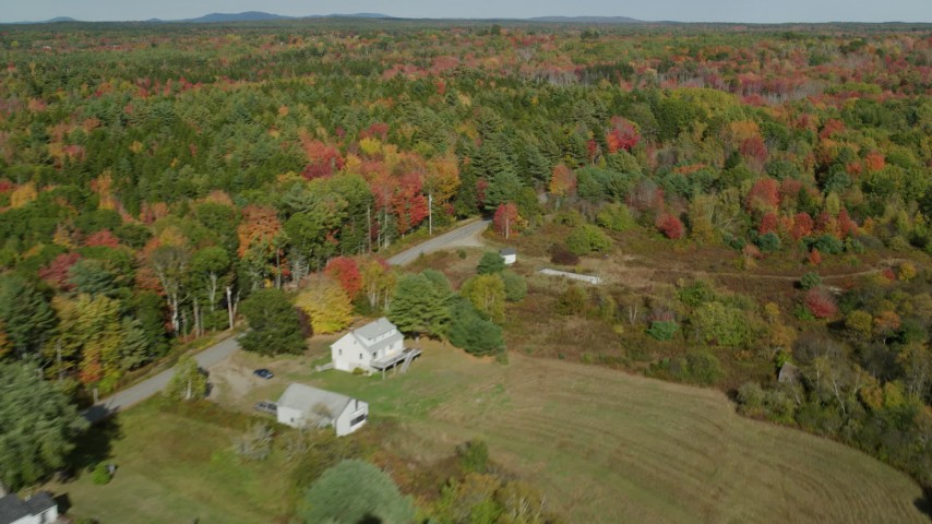 6k stock footage aerial video flying by a colorful forest, rural homes and road, autumn, Waldoboro, Maine Aerial Stock Footage | AX148_034