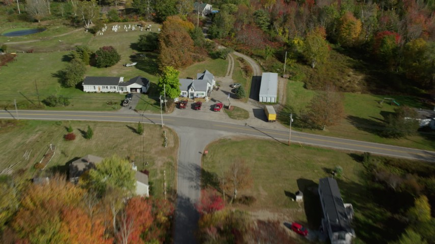 6k stock footage aerial video flying over rural road by homes in a colorful forest, autumn, Waldoboro, Maine Aerial Stock Footage | AX148_035