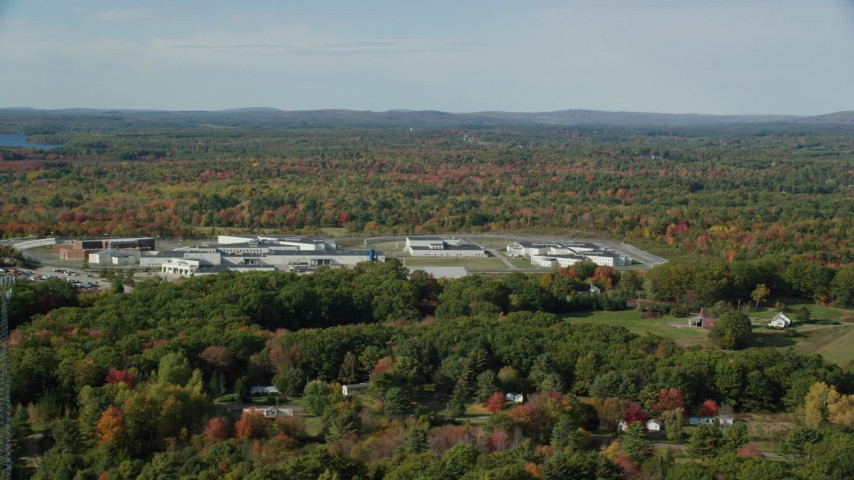 6k aerial video orbiting Maine State Prison, colorful forest, autumn, Warren, Maine Aerial Stock Footage | AX148_062