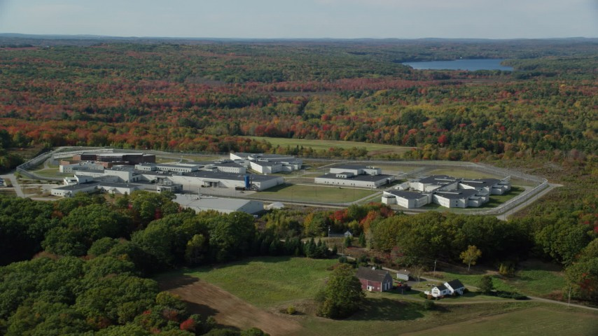 6k aerial video orbiting Maine State Prison, colorful forest, autumn, Warren, Maine Aerial Stock Footage | AX148_063
