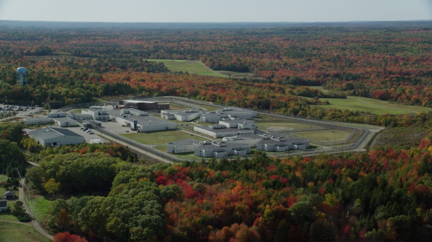 6k aerial video orbiting Maine State Prison, colorful forest, autumn, Warren, Maine Aerial Stock Footage AX148_064