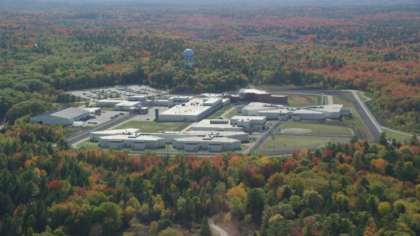 6k aerial video orbiting Maine State Prison, colorful forest, autumn, Warren, Maine Aerial Stock Footage | AX148_065