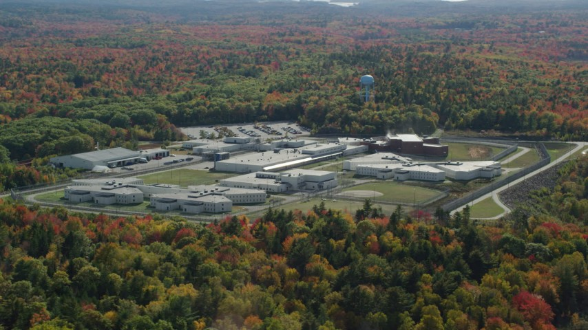 6k aerial video orbiting Maine State Prison, colorful forest, autumn, Warren, Maine Aerial Stock Footage | AX148_066